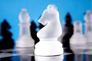 Glass chess knight on board