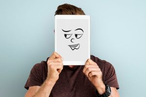 Man covering face with digital tablet