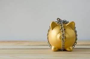 Gold piggy bank locked up in chains