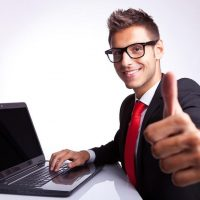 Businessman working on computer and showing thumbs up