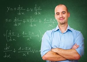 Male math teacher in front of a chalk board