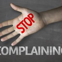 Stop complaining written on hand